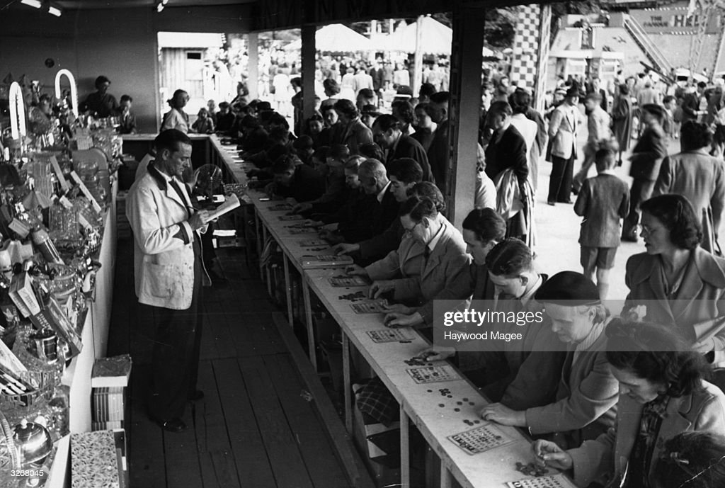 People playing bingo at a stall at the Festival Funfair in Battersea Park, London. Original Publication: Picture Post - 5323 - Fair Fun - pub. 1951