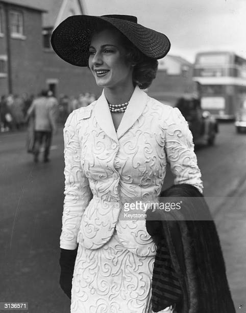On the first day of the Royal Ascot meeting, model Fiona Campbell Walter wears a black straw hat, a white corded suit and pearl necklace and is...