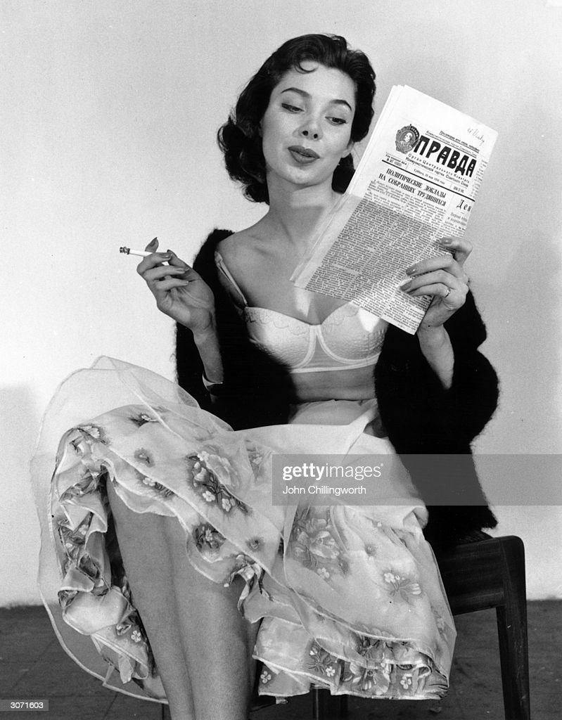 A Russian girl reads Pravda as she models British underwear in a sales campaign. Original Publication: Picture Post - 8420 - Some Pretty Things For Moscow - pub. 1956