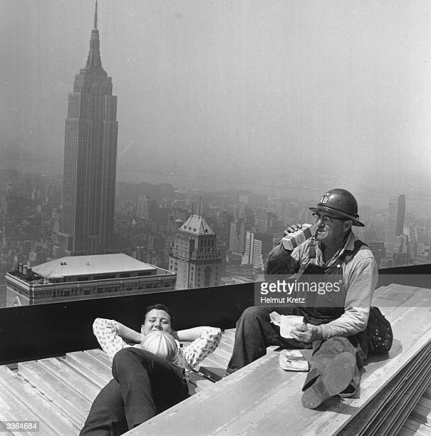 Constructions workers having a coffee break on the 59th floor of the Pan American building in New York The Empire State building is in the background