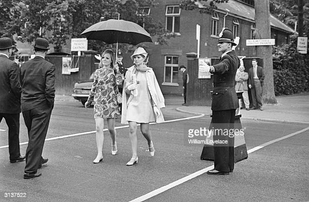 A policeman guides smartlydressed racegoers across the road at Ascot
