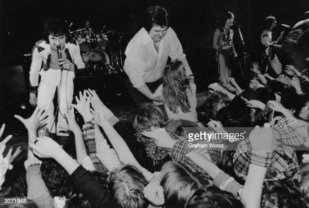 The Bay City Rollers whip screaming fans into a frenzy whilst being protected from their lusty clutches by a large security man during a concert in...