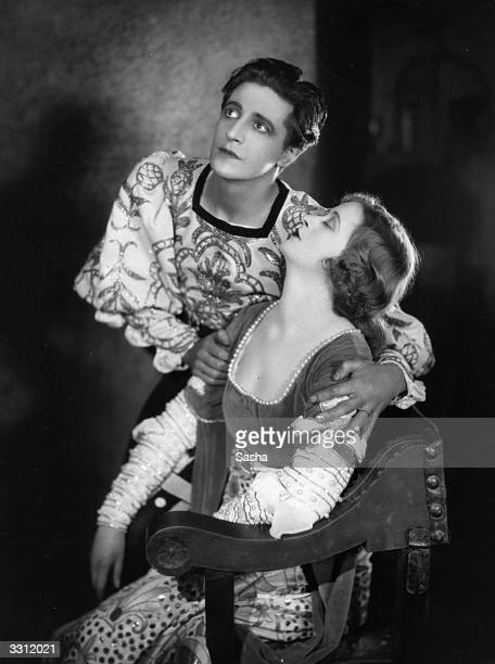 A sleeping Ursula Jeans is held by Welsh actor composer and dramatist Ivor Novello in a scene from the play `The Firebrand' at Wyndhams Theatre London