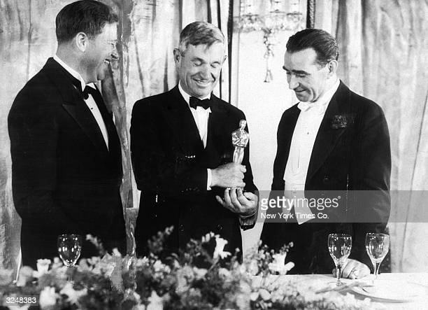 Left to right American sound engineer Franklin Hansen American actor and writer Will Rogers and Scottishborn director Frank Lloyd stand at the podium...