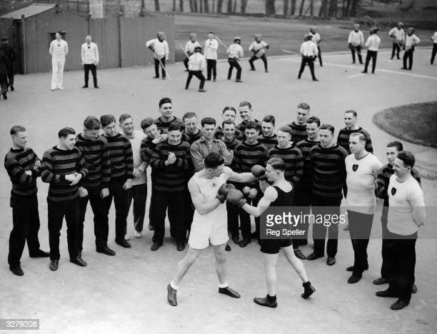 Boxing training at Aldershot with bayonet fighting practice in the background.
