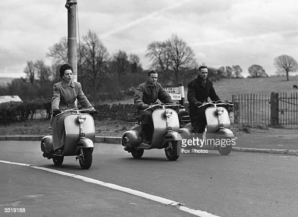 Three riders take the new Vespa motorcycle out on a road trial Built by the Douglas Company the bike is a copy of an Italian machine and is capable...