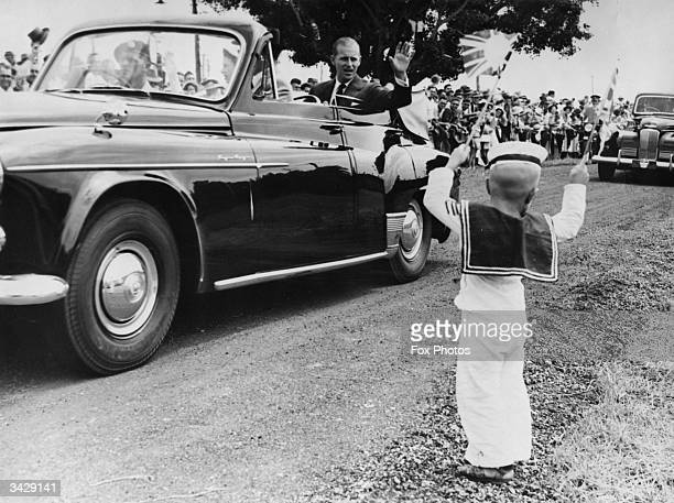 Seated beside Queen Elizabeth II the Duke of Edinburgh waves to an enthusiastic little sailor fouryearold Michael McCarthy during a tour of Mackay in...