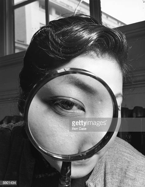 Miss Barbara Lee examining stamps through a magnifying glass at the National Stamp Exhibition at Central Hall in London's Westminster.
