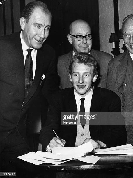 Denis Law signs for Manchester City FC at Hudderfield watched by Les McDowall and Doug Hamer Manchester City FC and Scottish International soccer...