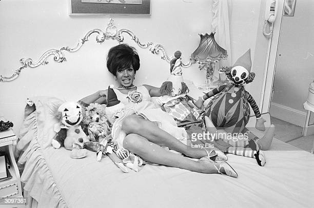 Welsh singer Shirley Bassey surrounded by toys on her bed.