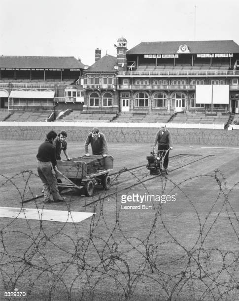 Ground staff at work on the artificial pitch at the Oval surrounded by barbed wire which has been erected temporarily to stop anti-apartheid...