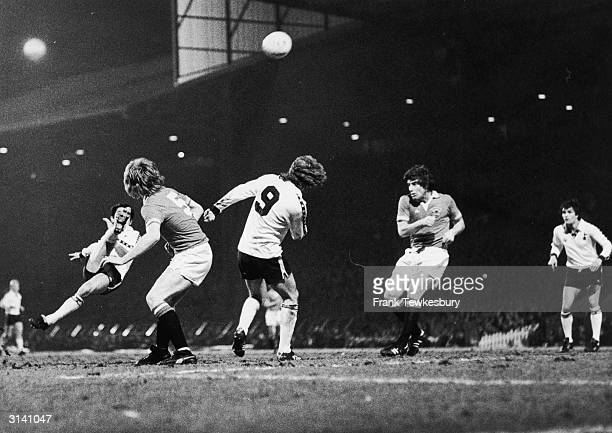 Manchester United footballers Gordon McQueen and Martin Buchan watch as the Tottenham Hotspur player Osvaldo Ardiles attempts an overhead kick
