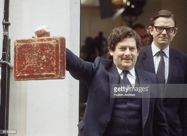 British Conservative politician journalist and Chancellor of the Exchequer Nigel Lawson holding the famous Budget Box aloft for the traditional...