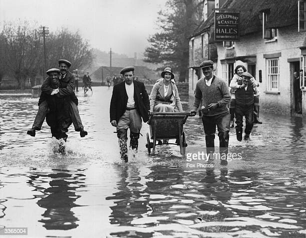Bampton village flooded, villagers helping each other to evacuate.