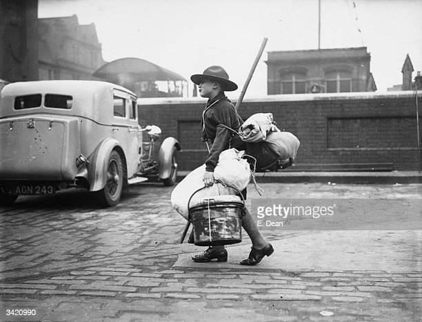 A Boy Scout laden with his camping equipment arriving at Waterloo Station London