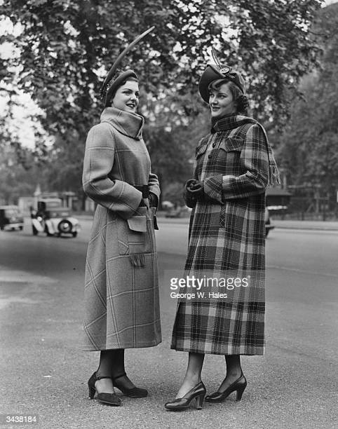 Two women modelling tailored coats of blue and white checked tweed and olive green tweed with a scarf collar during London's Fashion Fortnight