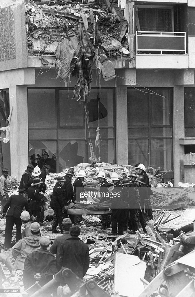 Firemen carrying a victim recovered beneath debris at the site of the collapsed tower block, Ronan Point, Canning Town, London.
