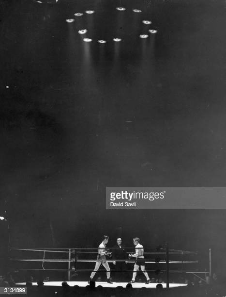 The referee stands framed by two boxers in a ring at the NSC