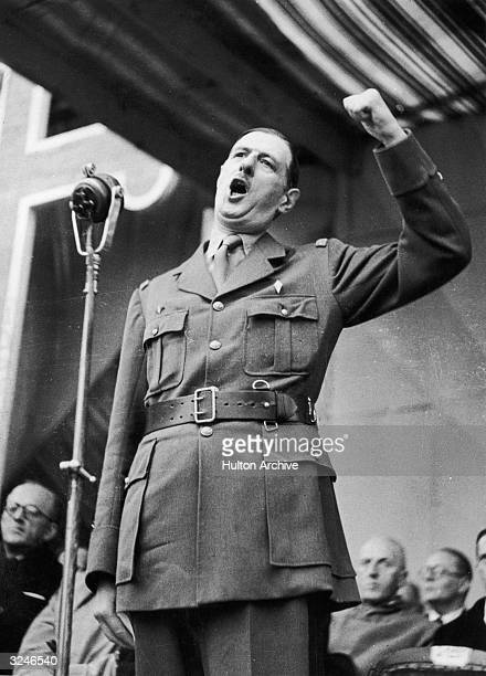 French general and statesman Charles de Gaulle raises his fist as he delivers an address at the end of the Allied Armistice Day parade in Algiers...