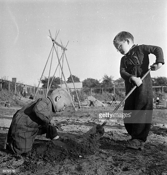 Young children helping each other to build mud castles in the experimental playground allotted to them on an abandoned wasteground in Emdrup...