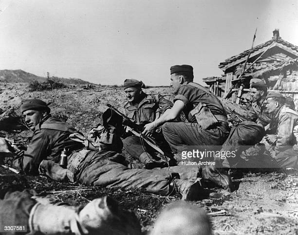 Men of the Argyle and Sutherland Highlanders take cover as they advance into the town of Chonju on the British front in North Korea during the Korean...