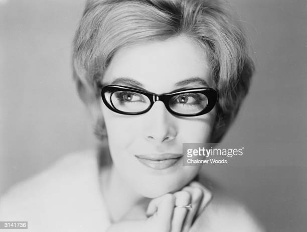 A serene looking woman resting her chin on her hand while modelling thick black framed glasses