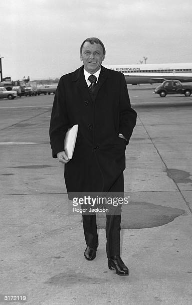 Frank Sinatra arrives at Gatwick airport to attend a charity concert alongside Bob Hope at the Royal Festival Hall