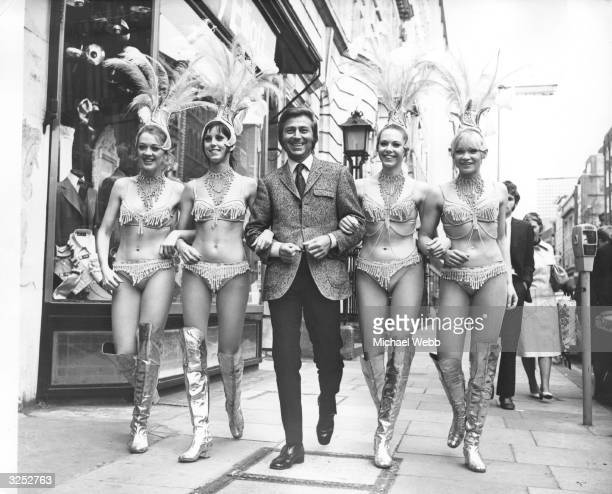 British variety performer Des O'Connor with some of the chorus line from the London Palladium Variety Show.
