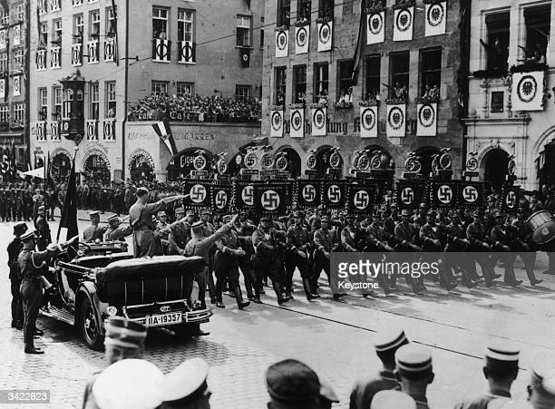 German dictator Adolf Hitler salutes Nazis as they march past during a parade in Nuremberg