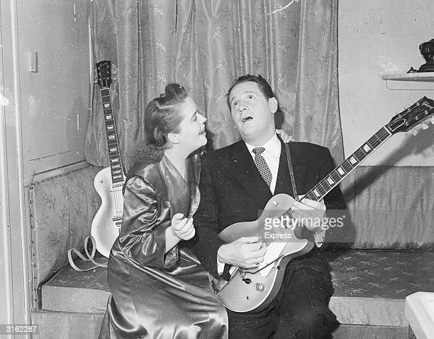 Popular guitarist Les Paul serenades his wife and singing partner Mary Ford