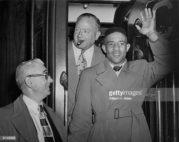British boxer Randolph Turpin arrives at Waterloo Station in London with promoter Jack Solomons