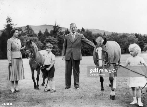 From left to right Queen Elizabeth II Prince Charles Prince Philip Duke of Edinburgh and Princess Anne with two ponies in the grounds of Balmoral...