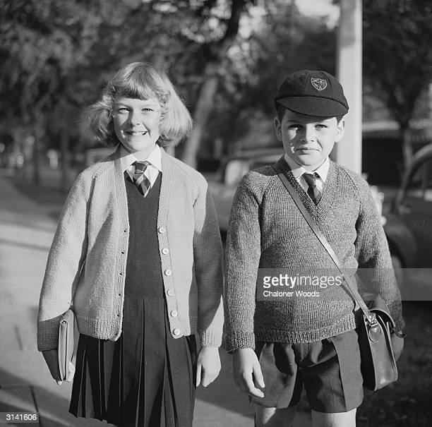 A young schoolgirl wears a knitted cardigan over a shirt and gymslip the schoolboy with her wears a long sleeved vnecked pullover with shorts and a...