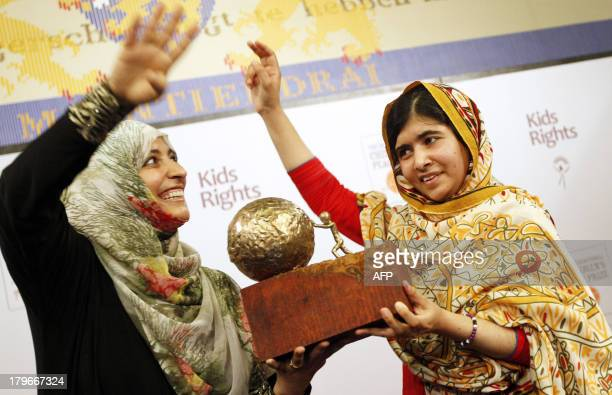 16year old Malala Yousafzai from Pakistan receives a trophy from Yemeni Civil Rights activist and 2011 Nobel Peace Prize winner Tawakkul Karman after...