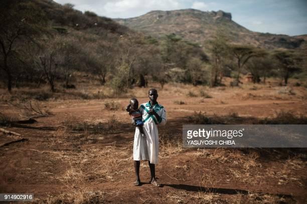 TOPSHOT 16yearold Chematu Cheraiman who has not undergone female genital mutilation holds her one and half year old son in Katabok village northeast...