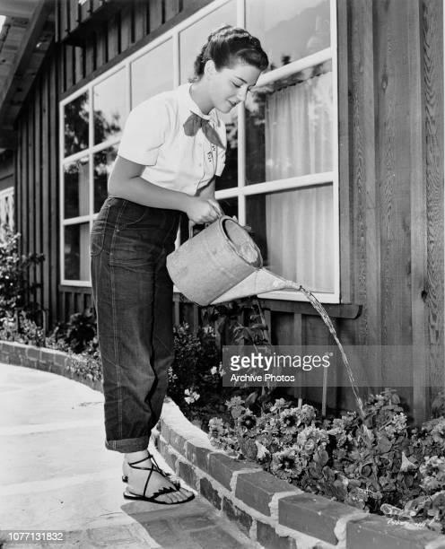16yearold Italian operatic soprano Anna Maria Alberghetti watering the plants at her home in California 25th September 1952