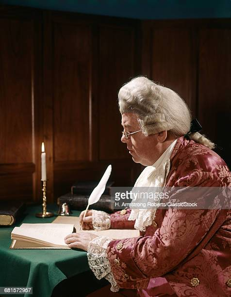 1770s MAN DRESSED LIKE BENJAMIN FRANKLIN IN 1776 COLONIAL COSTUME SITTING WRITING WITH QUILL PEN