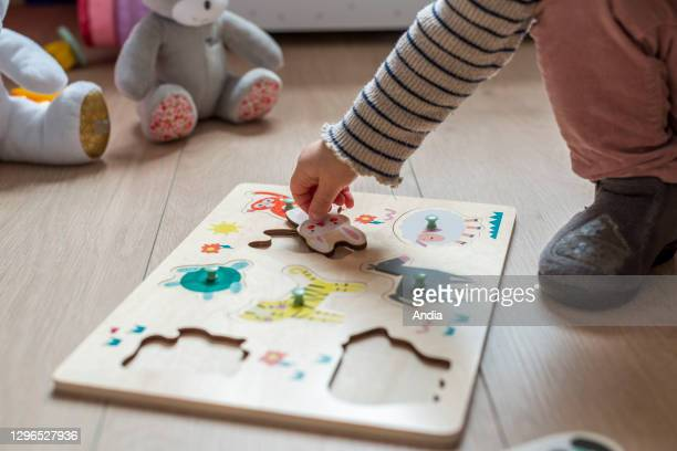 Month child playing with a wooden jigsaw puzzle, fitting shapes of animals.