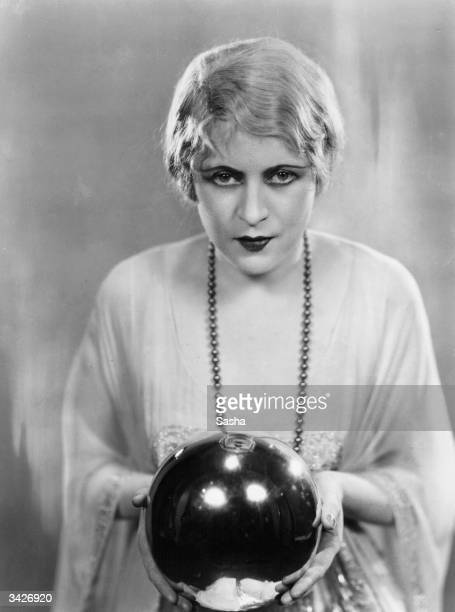 Ruby Miller holding a crystal ball in a scene from the play 'The Monster' at the Strand Theatre London