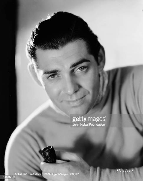 American actor Clark Gable holding a pipe.