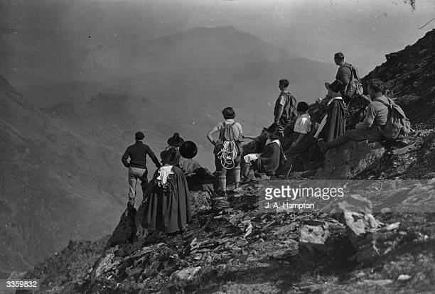 Group of women wearing the Welsh national costume accompanying a party of climbers ascending Mount Snowdon, North Wales, at Easter.
