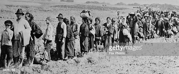 Okinawa civilians returning from hiding places in the hills following the invasion of the island by American soldiers.
