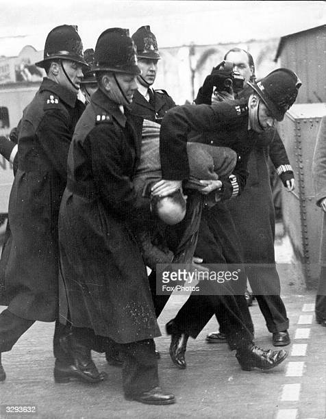 As the trial of seven dockers at the Old Bailey nears its close one of the crowd of sympathisers waiting outside the court is escorted away by the...