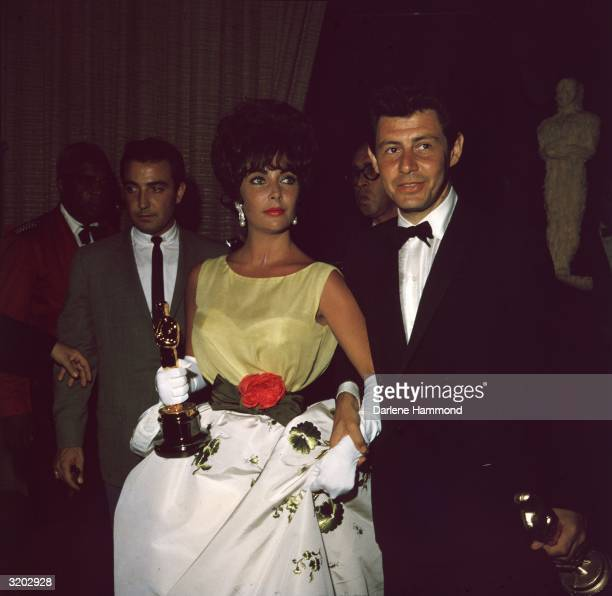 British-born actor Elizabeth Taylor, holding the Oscar she won for best actress in director Daniel Mann's film, 'Butterfield 8,' with husband,...