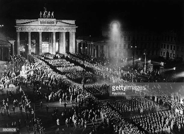 Nazi SA troops parading through the Brandenburg Gate at night in Berlin during the filming of a reenactment of the scene at Hitler's appointment as...