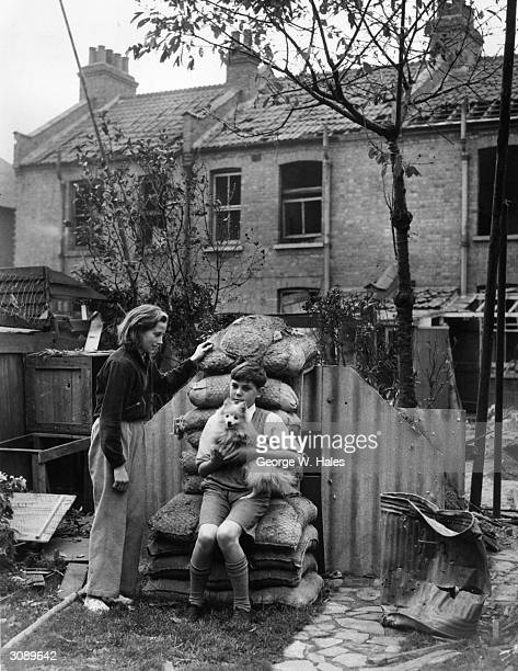 Raymond Burrell with his neighbour and pet dog by the shelter in which they took refuge when German raiders dropped bombs in southwest London
