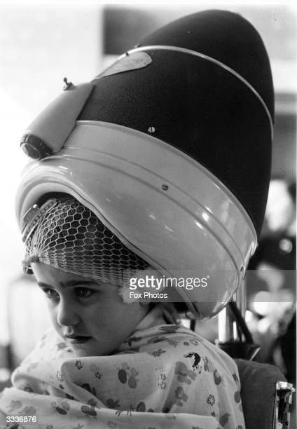 Four-year-old Susan Wolf waits stoically under a hairdryer at the Children's Beauty Parlour at Selfridges department Store in Oxford Street, London.