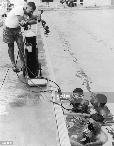 Coach Forbes Carlisle watches as three members of the Australian swim team use masks to inhale oxygen from a tank at the side of Tobruk Memorial...