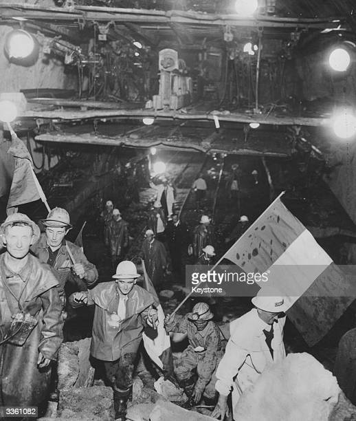 Workers from the French side of the Mont Blanc tunnel project scramble over freshly blasted rock to the exposed Italians The project has taken 35...