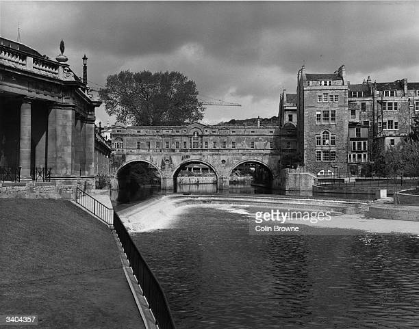 The recently completed weir on the river Avon at Bath near the famous Pulteney Bridge with its arcade of shops over the river